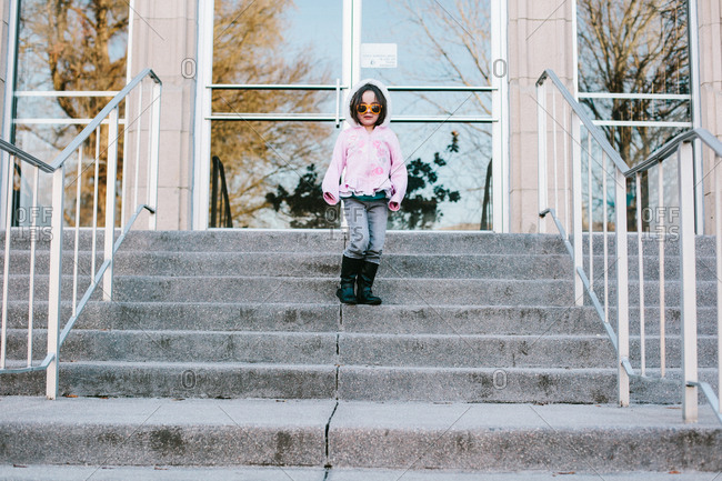 Girl in sunglasses standing on stairs
