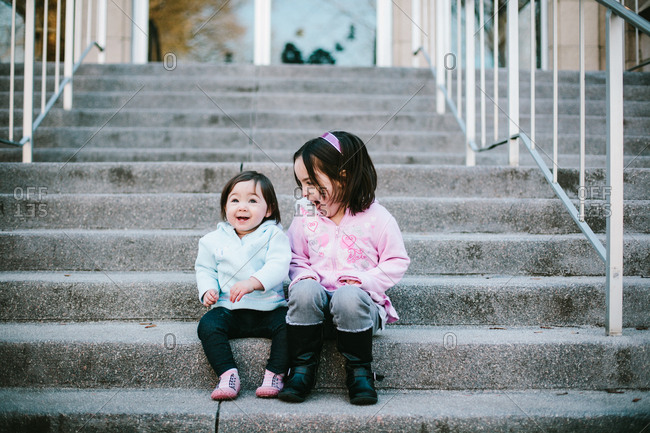 Preschooler sitting on stairs with toddler outside