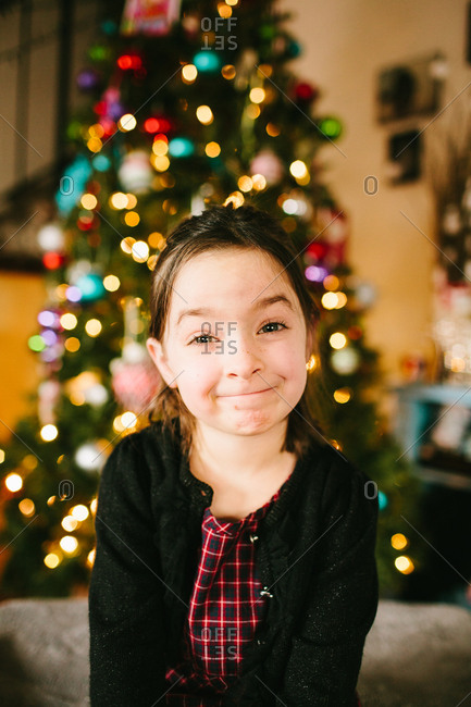 Little girl smiling in front of a Christmas tree