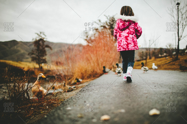 Girl by ducks and a pond