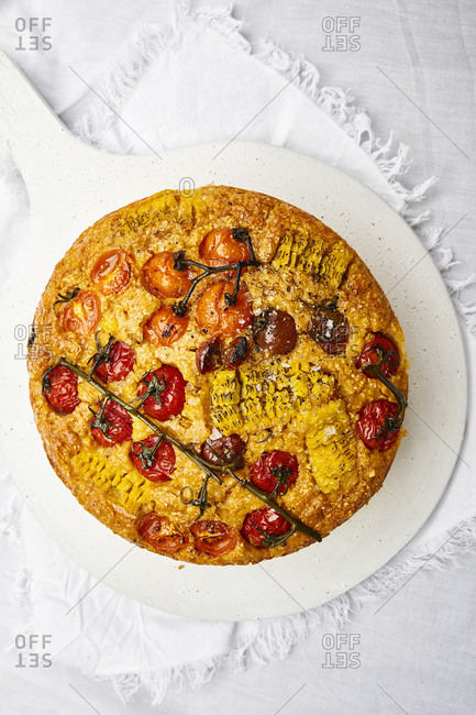 Sweet cornbread with vine tomatoes on white serving board and white linen.