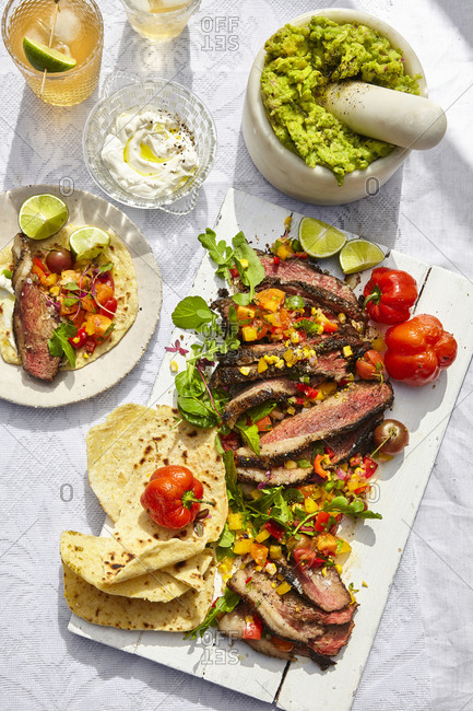 Juicy grilled steak on the bbq thinly sliced served with homemade soft tacos, grilled corn salsa and guacamole