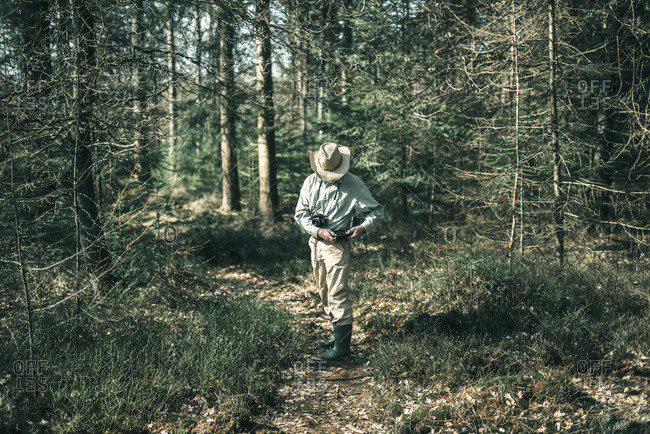 Man with hat in forest grabbing binocular out of bag.