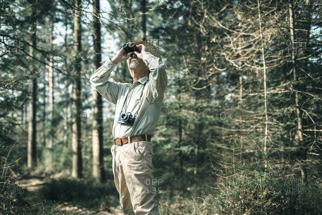 Man looking with binocular in forest.