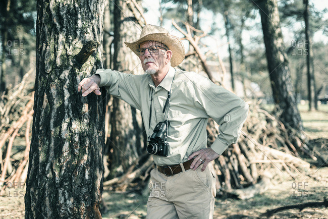 Senior male nature photographer wearing hat leaning against tree.