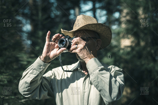 Man with straw hat photographing nature in forest.
