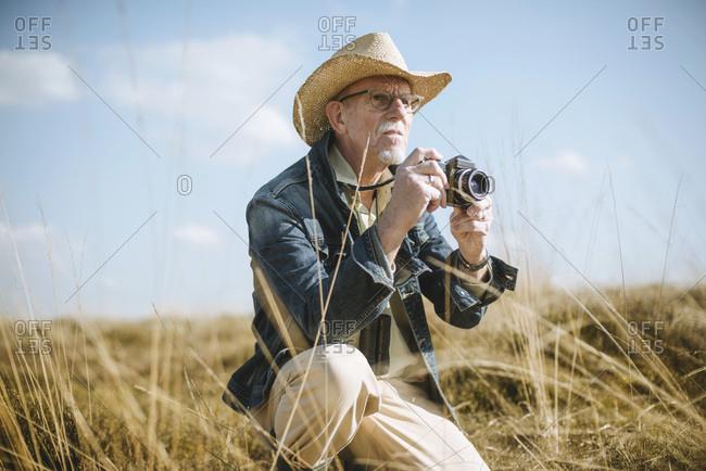Safari man sitting with camera in field.