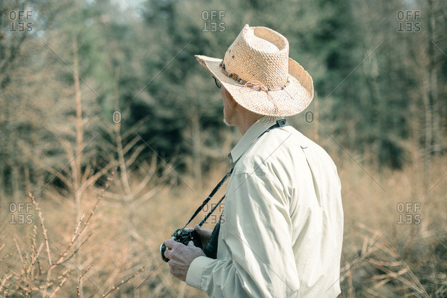 Retired man with camera standing in nature. Rear view.