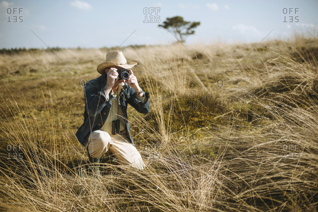 Safari man sitting with camera in field.