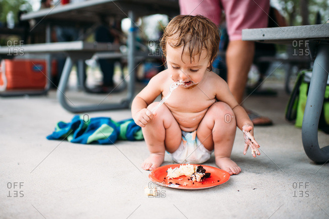 Toddler in diaper eating birthday cake on a red plate.