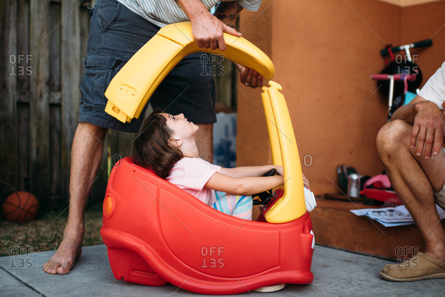 Little girl sitting in plastic car while her father puts it together.