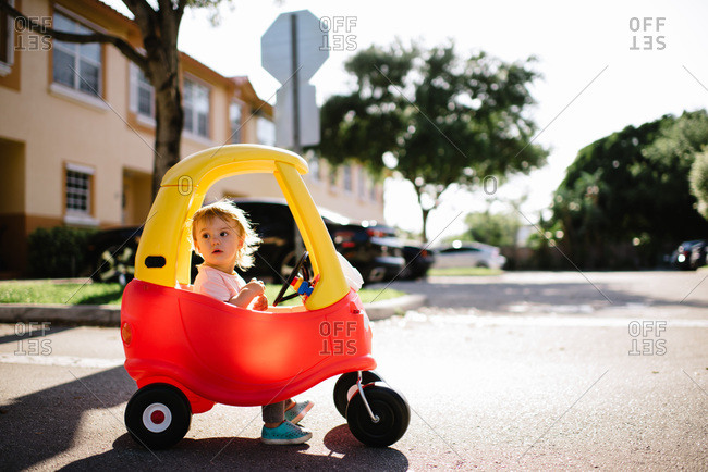 Toddler girl sitting inside a toy car in a parking lot.