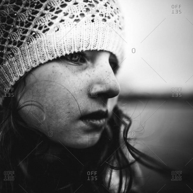 Close up portrait of young girl with freckles in winter hat