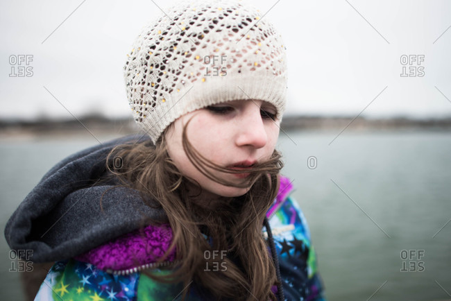 Young girl in winter hat with hair blowing across her face
