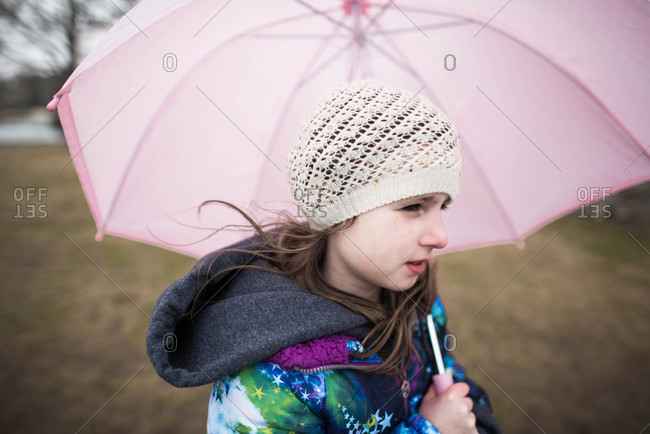 Young girl carrying a pink umbrella