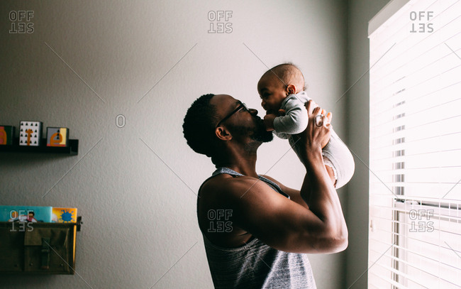 Father kissing his newborn son in bedroom