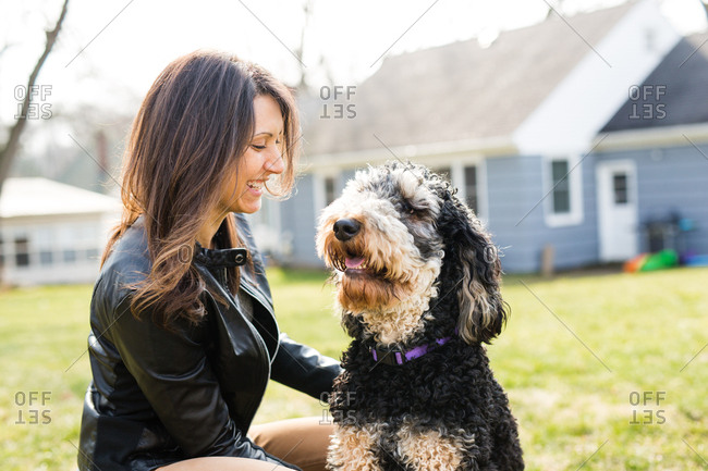 Smiling woman next to Golden doodle dog