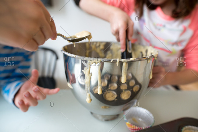 Children scooping spoonfuls of muffin batter from mixing bowl