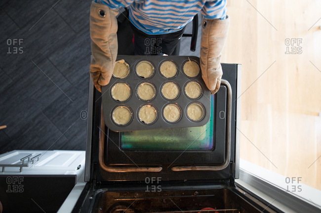 Boy wearing oven mitts putting muffin tin into oven
