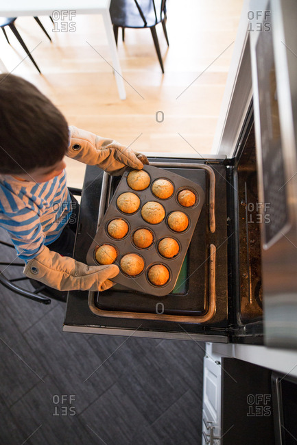 Boy wearing oven mitts taking pan with freshly baked muffins out of the oven