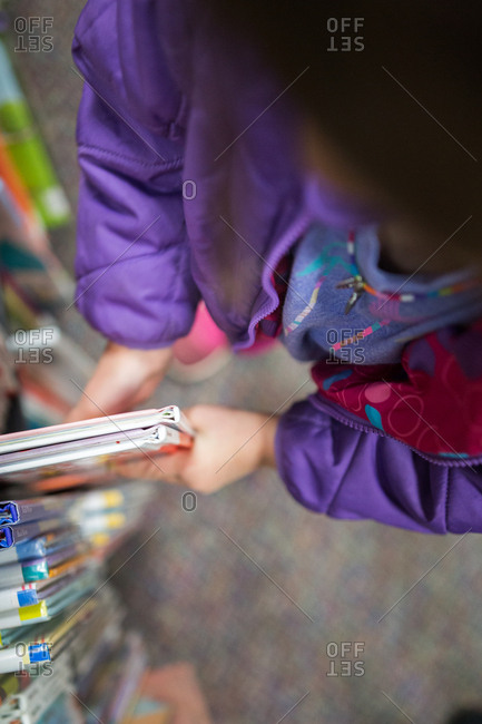Child pulling books off the shelf at library