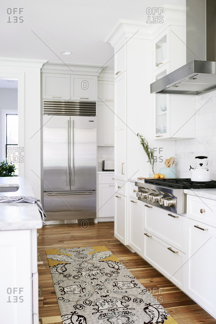 Kitchen with white cabinets and marble countertops