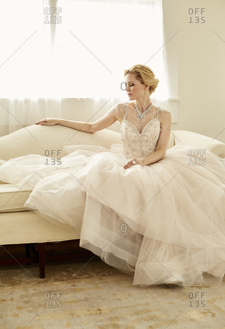 Portrait of seated bride on white sofa