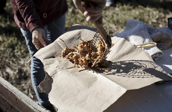 Cook dumping basket of fried food on brown paper