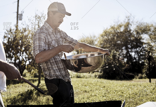 Virginia, USA - October 23, 2016: Man with mixing bowl cooking outdoors