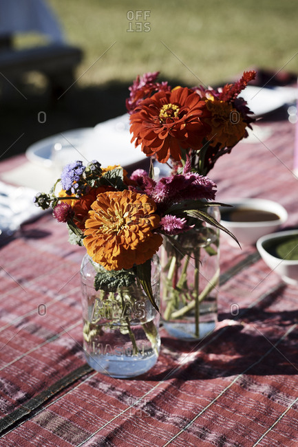 Virginia, USA - October 23, 2016: Glass jars of flowers on outdoor dining table