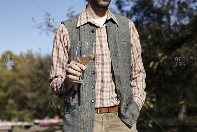 Man in plaid shirt and tweed vest with glass of wine