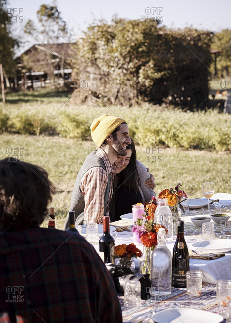 Virginia, USA - October 23, 2016: Affectionate couple at table at outdoor dinner