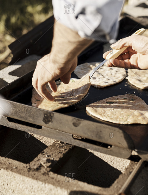 Chef cooking flatbread on outdoor grill
