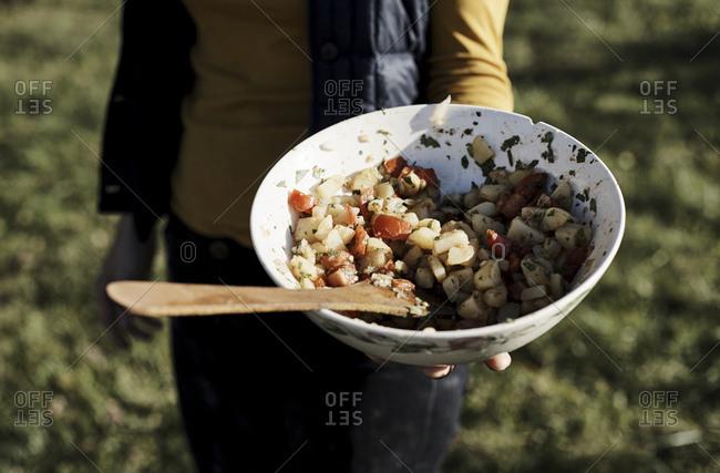 Person holding bowl of potato salad