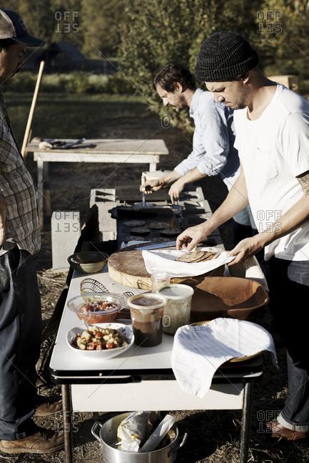 Virginia, USA - October 23, 2016: Man watching people preparing food outdoors