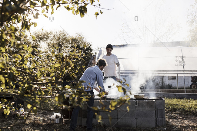 Virginia, USA - October 23, 2016: Two men cooking at outdoor grill