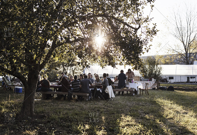 Virginia, USA - October 23, 2016: People at an outdoor dinner party on farm at dusk