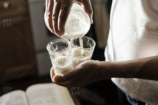 Man pouring two glasses of a drink from a jar