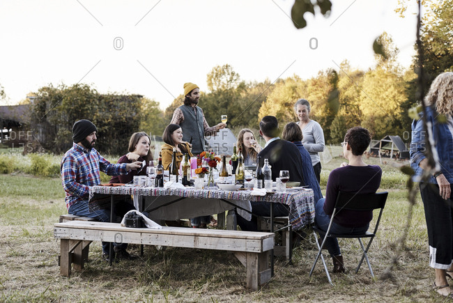 Virginia, USA - October 23, 2016: Friends having conversation at outdoor dinner party at dusk