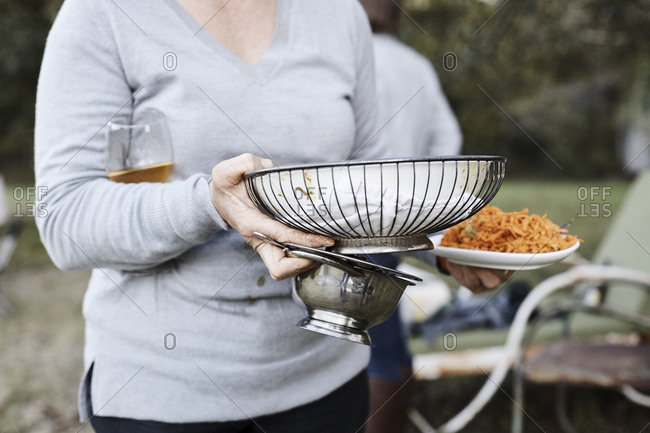Woman with hands full carrying serving dishes at outdoor dinner