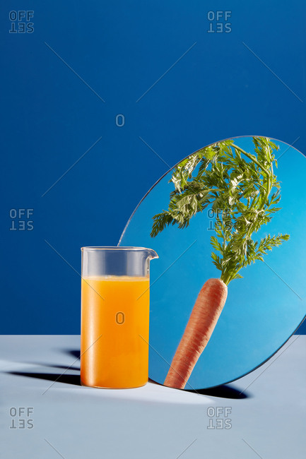 Glass of freshly squeezed juice reflected in mirror as a carrot