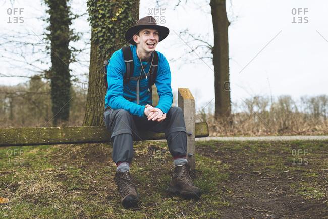 Smiling hiker with hat resting on fence in rural landscape.