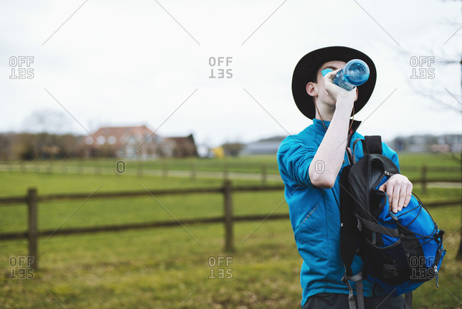 Thirsty hiker drinking from water bottle in rural landscape.