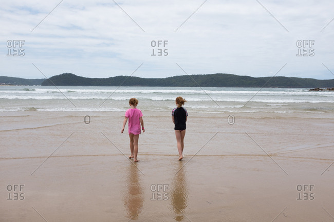 Two young girls walking towards the ocean