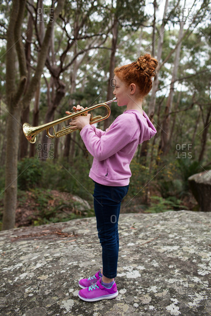 Young girl playing the trumpet in the bush