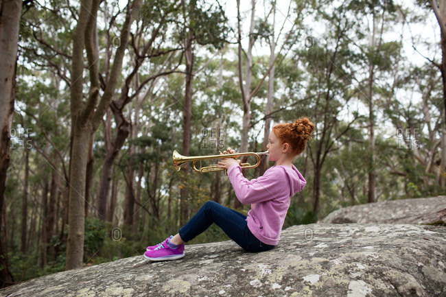 Young girl playing the trumpet while sitting on a rock