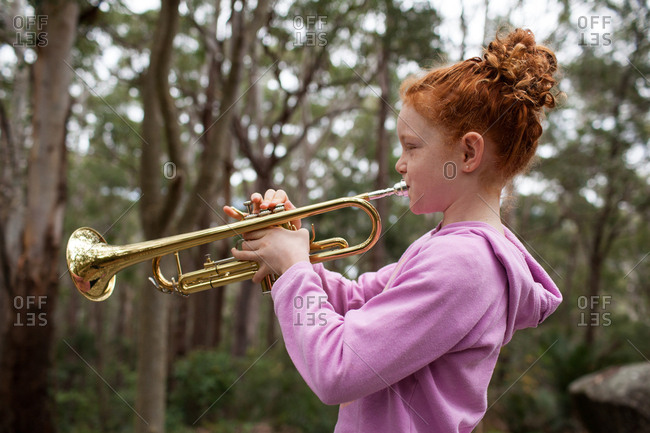 Close up of a young girl playing the trumpet outside