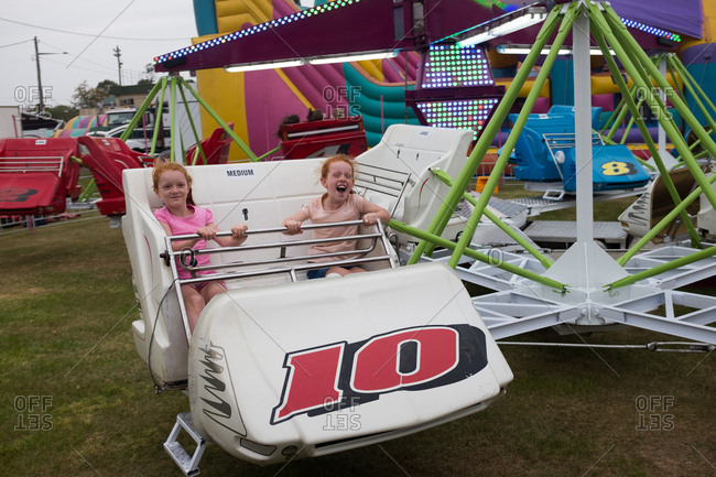 Lismore, NSW, Australia - October 22, 2016: Two young girls having fun on an amusement ride