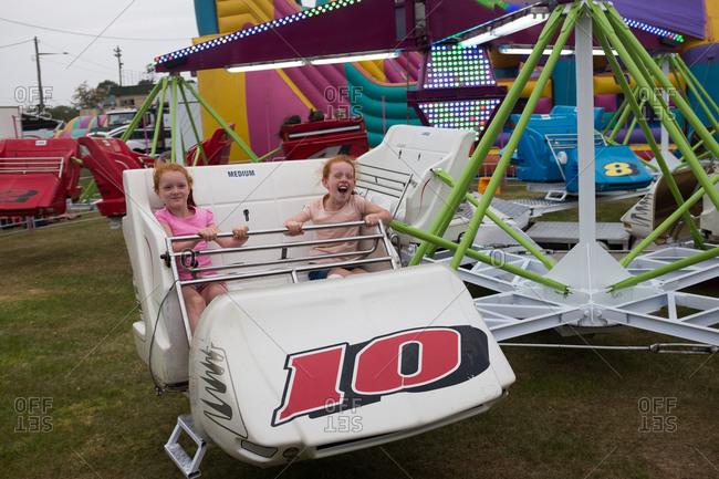 Lismore, NSW, Australia - October 22, 2016: Two young girls having fun on an amusement ride