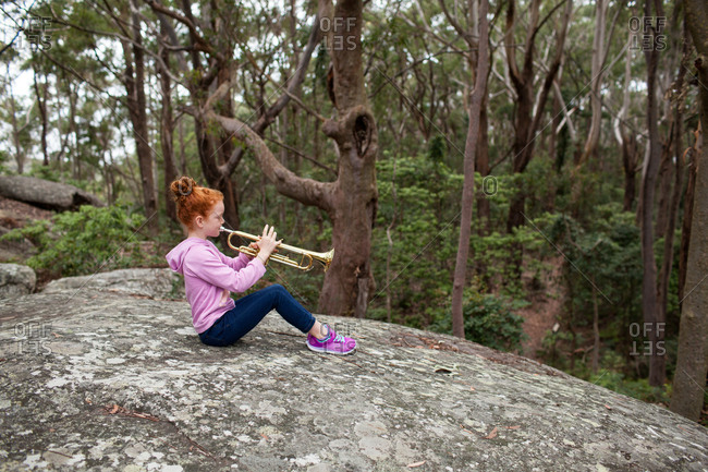 Young girl playing the trumpet sitting on a rock